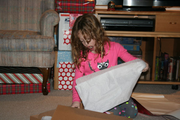 Irene unwrapping her Santa gift