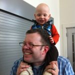 Sam the Anti-Preemie sitting on dad's shoulders